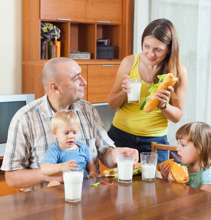 gladful: Happy parents and two children having lunch with sandwiches at the table