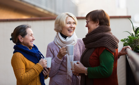señora mayor: Retrato de alegres amigos femeninos mayores que beben el café en el patio. Centrarse en rubia