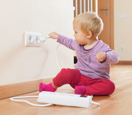 Toddler playing with electrical extension and   outlet at home