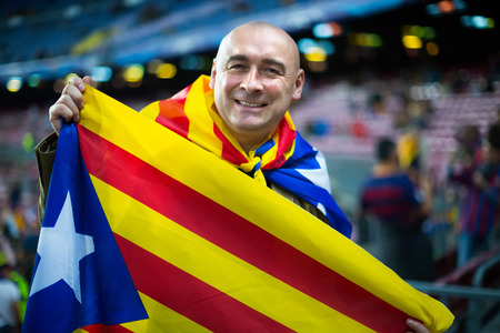 fandom: Happy smiling male football fan with flag of Catalonia at crowded stadium