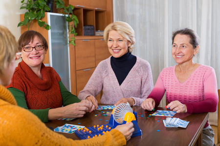55 60: Several happy female pensioners playing board game in the home