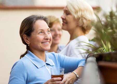 55 60: Smiling senior female colleagues having lunch break at patio Stock Photo