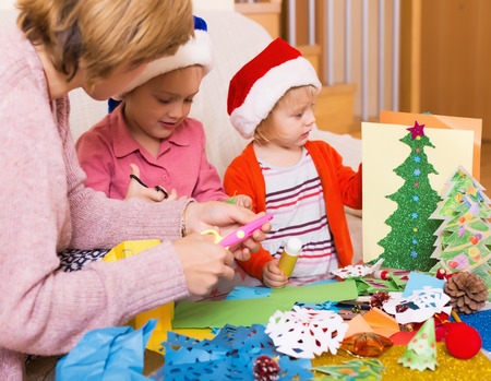 3 5 years: Young mother helping  two girls to make decoration for Xmas  at home