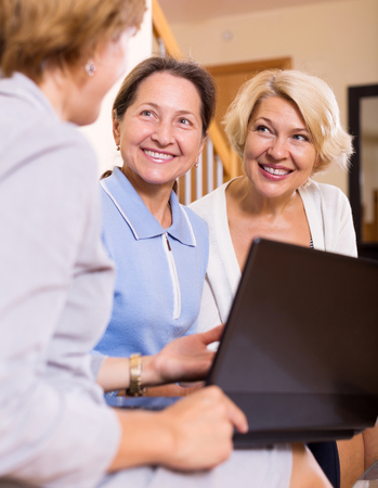 55 60: Insurance agent consulting female pensioners at home Stock Photo