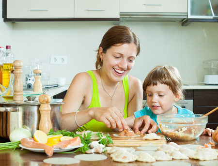 red  fish: Girl leisurely makes dumplings with red fish in a home kitchen Stock Photo