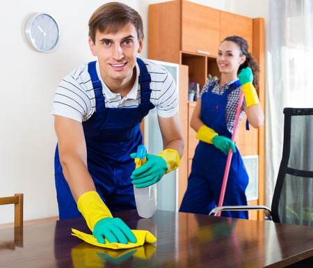 25 30: Positive couple in uniform smiling and cleaning indoors