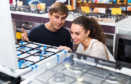 hobs: Ordinary family choosing gas hobs in hypermarket and smiling Stock Photo