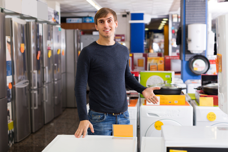 hobs: Portrait of ordinary young man at household appliances store Stock Photo