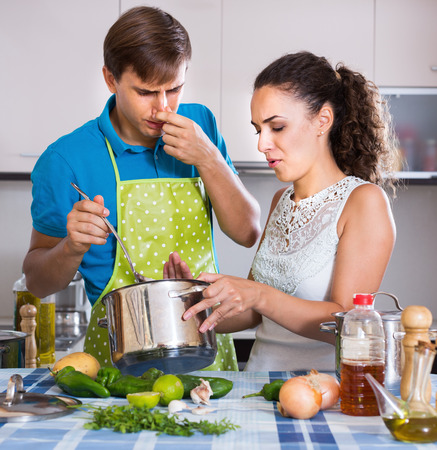 stinking: Portrait of young couple with stinking food in domestic kitchen