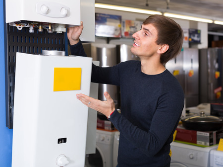25 35: Smiling male customer looking at domestic boilers Stock Photo