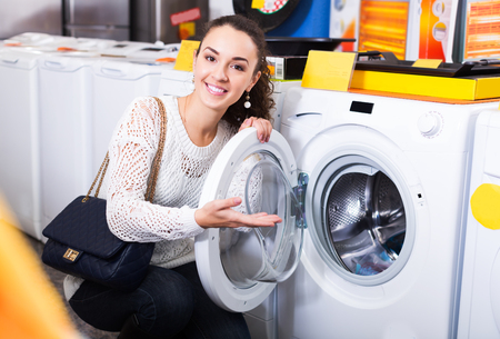 average woman: Average woman customer looking at washers and dryers in store