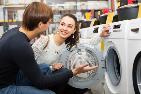 lavadora con ropa: Happy young family couple buying new clothes washer in supermarket
