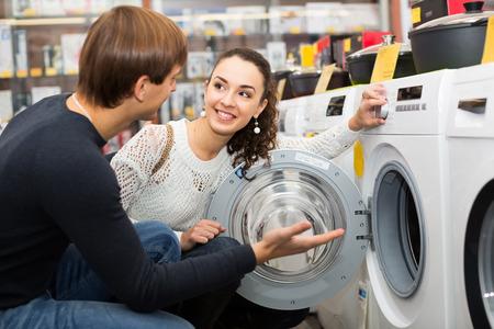 lavadora con ropa: Pareja joven familia feliz comprar nueva lavadora de ropa en un supermercado Foto de archivo