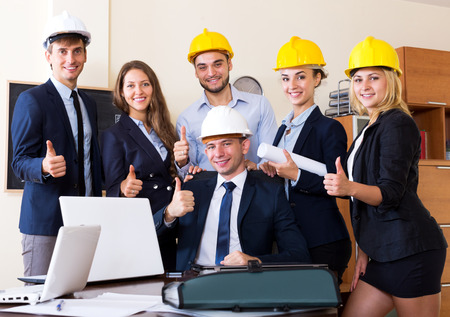 co operation: Smiling team of architectural engineers with laptops and blueprints in office