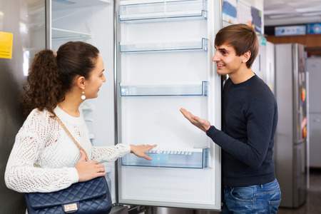 domestic appliances: Customers choosing new large fridges in domestic appliances section in store