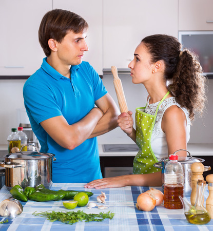 Unpleased person having quarrelling young spouse in domestic kitchen