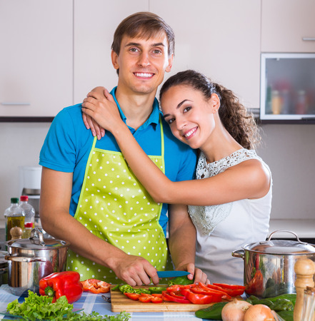 young wife: Happy young man in apron helping smiling wife to prepare healthy dinner