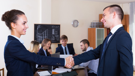 co operation: Firm handshake between two russian business partners at office meeting