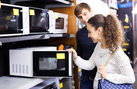 newly married: Newly married couple selectin microwave oven in hypermarket and smiling