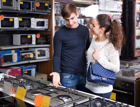 Jeune couple de famille sélectionner nouvelle cuisinière à gaz dans les appareils boutique Banque d'images