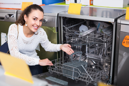 domestic appliances: Average female customer looking at dishwashers in domestic appliances store indoors