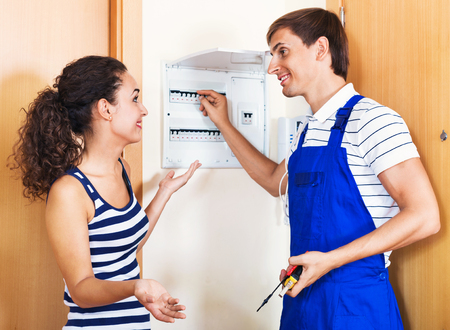 electric meter: Beautiful smiling woman and repairman near electric meter in domestic interior