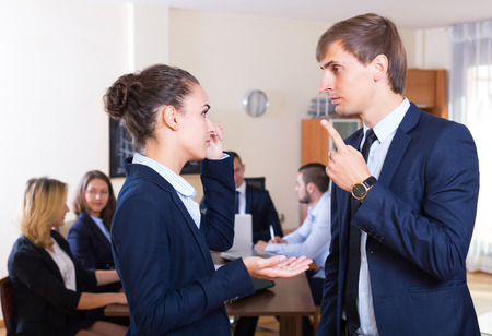Manager severely lecturing upset employee for mistake at office meeting Stock Photo