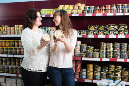 canned goods: Smiling mature and young customers choosing canned goods in food store