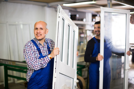 glasswear: Two smiling professional workmen in coverall with different PVC windows and doors Stock Photo