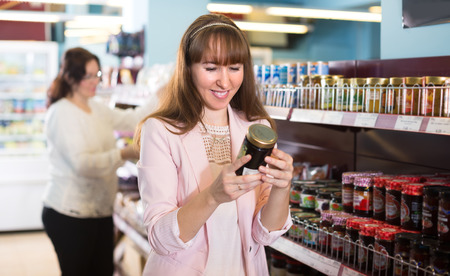 55 60: Two friendly smiling female customers choosing confiture in food store