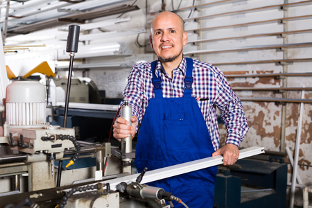 toiling: Friendly smiling middle-aged workman in coverall toiling on a machine in PVC shop Stock Photo