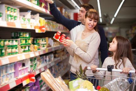 25 35: positive spanish family couple and girl choosing sweet pudding and smiling