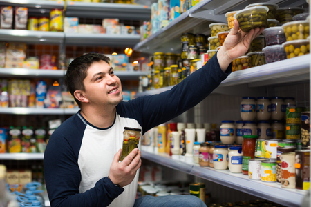 tinned: Positive smiling young man buying tinned food at grocery store