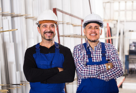 specialists: Crew of specialists in helmets and workwear posing at workshop . Selective focus Stock Photo