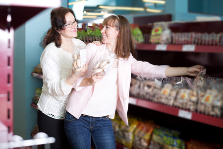 55 60: Smiling mature and young customers choosing pastry in food store Stock Photo