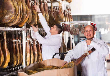 technologists: Ordinary Butchery technologists in white gown checking joints of iberico jamon
