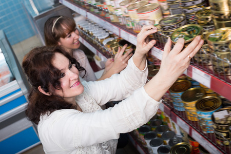 tinned: Happy female customers selecting tinned products at grocery Stock Photo