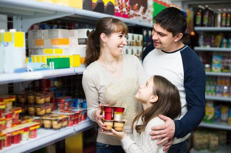ordinary: Ordinary spanish customers choosing dairy products and smiling in hypermarket Stock Photo