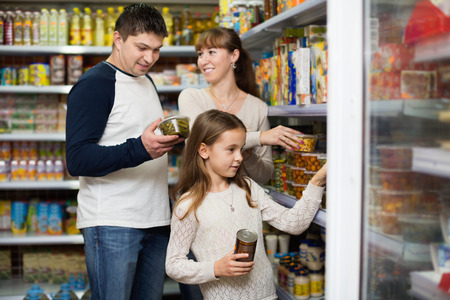tinned: Happy parents with little girl buying tinned food at grocery Stock Photo