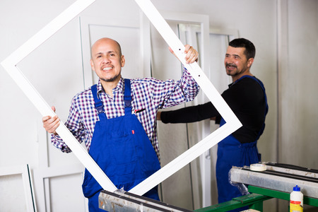 glasswear: Professional workmen with finished PVC profiles and windows at factory Stock Photo