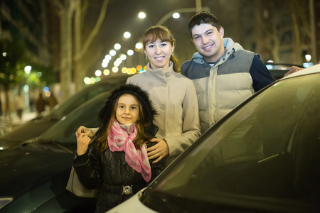25 35: Happy family with girl posing near car outdoors in winter