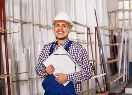 examiner: positive american male surveyor in coverall doing checkup and filling papers