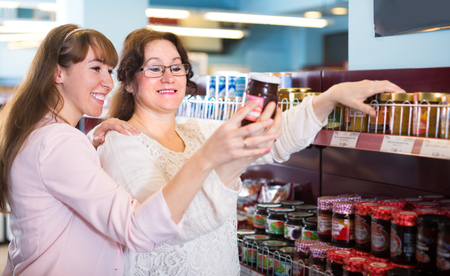 confiture: Two happy smiling female customers choosing confiture in food store