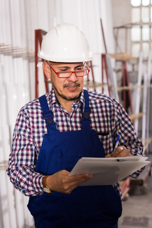 rigger: happy russian male surveyor in coverall doing checkup and filling papers Stock Photo