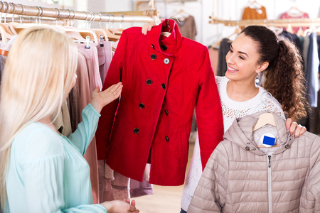 selecting: Attractive young female customers selecting coats and jackets at the shop