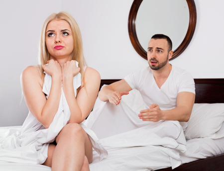 complaining: Sad beautiful young woman turned away from man complaining in bed Stock Photo