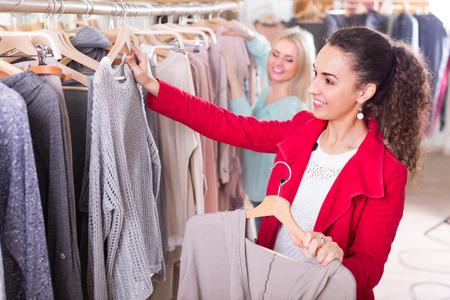 Dos mujeres jóvenes alegres que eligen prendas básicas en la tienda de ropa