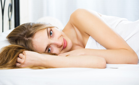 wellness sleepy: Young woman lying in bed with opened eyes and smiling