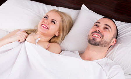 having sex: Happy young couple smiling in bed after having sex
