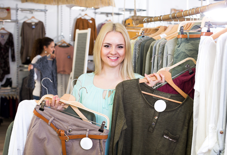 garments: Cheerful blond female customer selecting new garments at the store